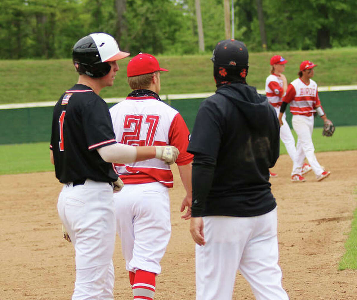 Edwardsville coach Tim Funkhouser gets a fist bump from his son and Tigers shortstop Evan Funkhouser at third base during a game last season at Alton High in Alton.