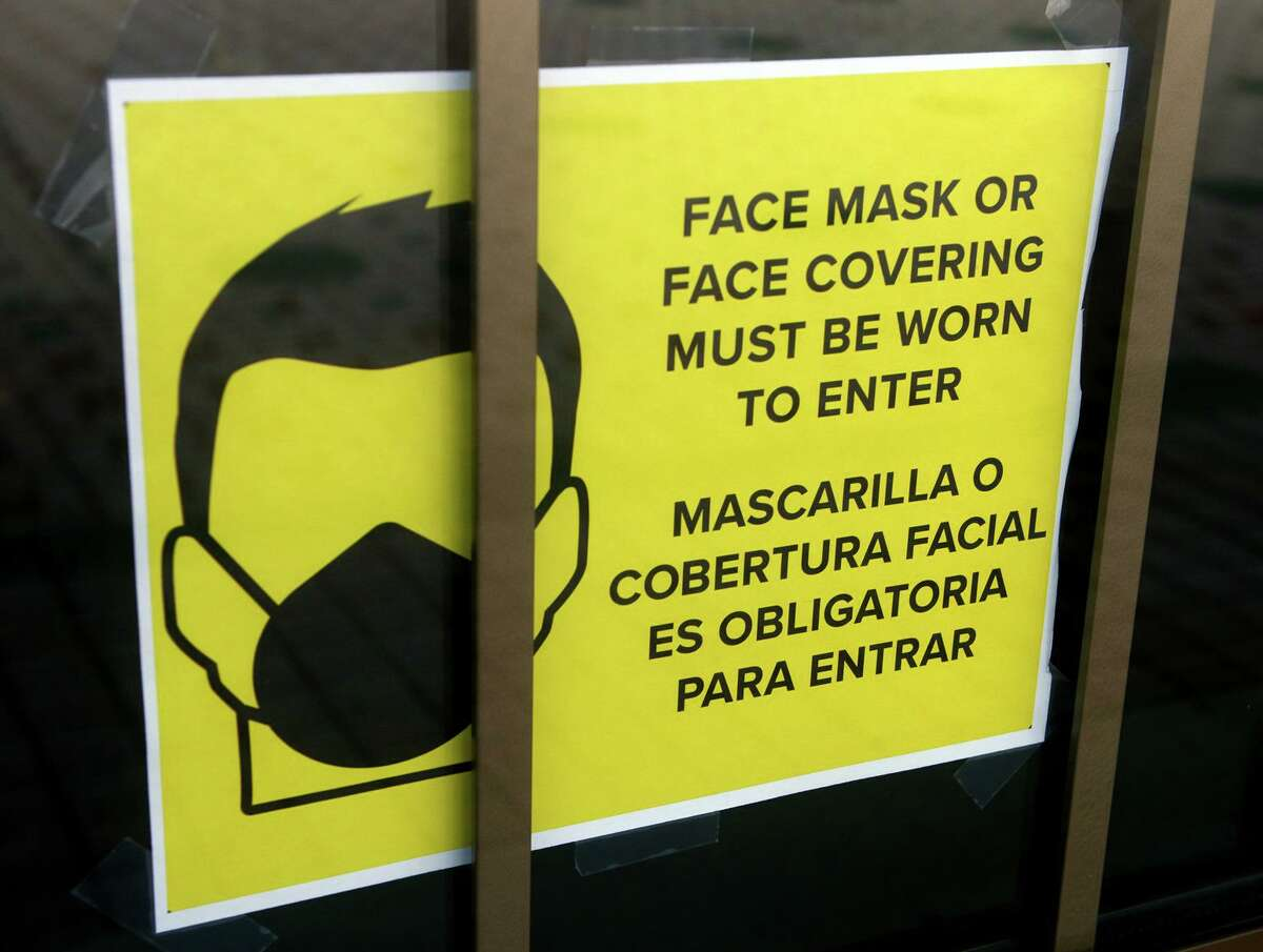 A sign requiring masks or face covering hangs on the front door of the Morton Government Center in Bridgeport on Aug. 11.