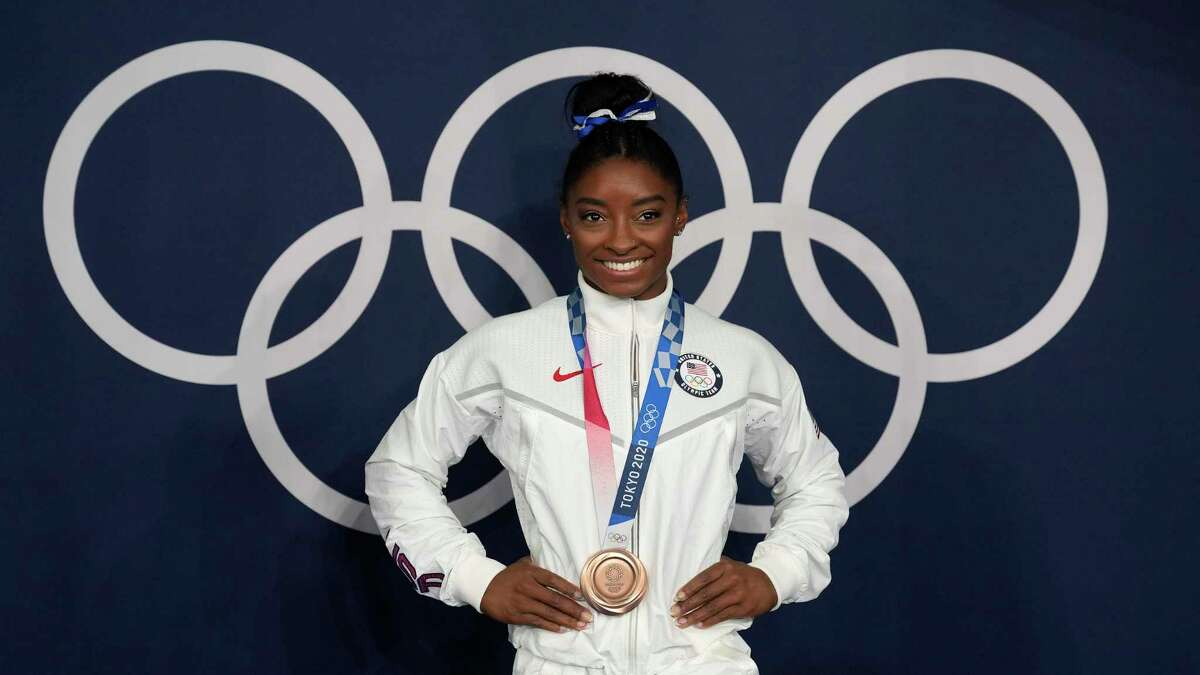 Simone Biles, of the United States, poses wearing her bronze medal from balance beam competition during artistic gymnastics at the 2020 Summer Olympics on Aug. 3 in Tokyo.