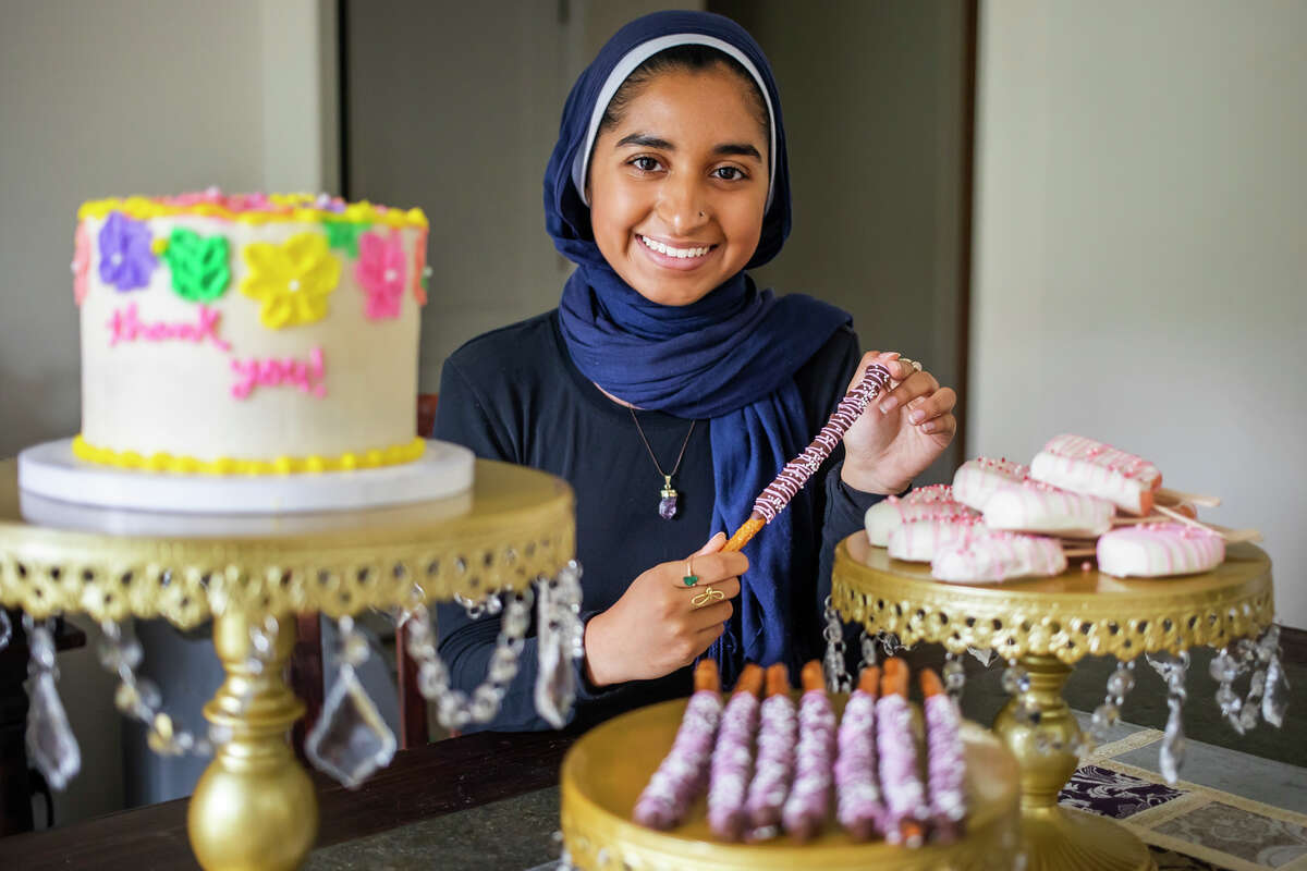 Fatimah Khan poses for a portrait with some of the confectionary creations she sells for her business, Chocoletzle, Tuesday, Aug. 10, 2021 at her home in Midland. (Katy Kildee/kkildee@mdn.net)