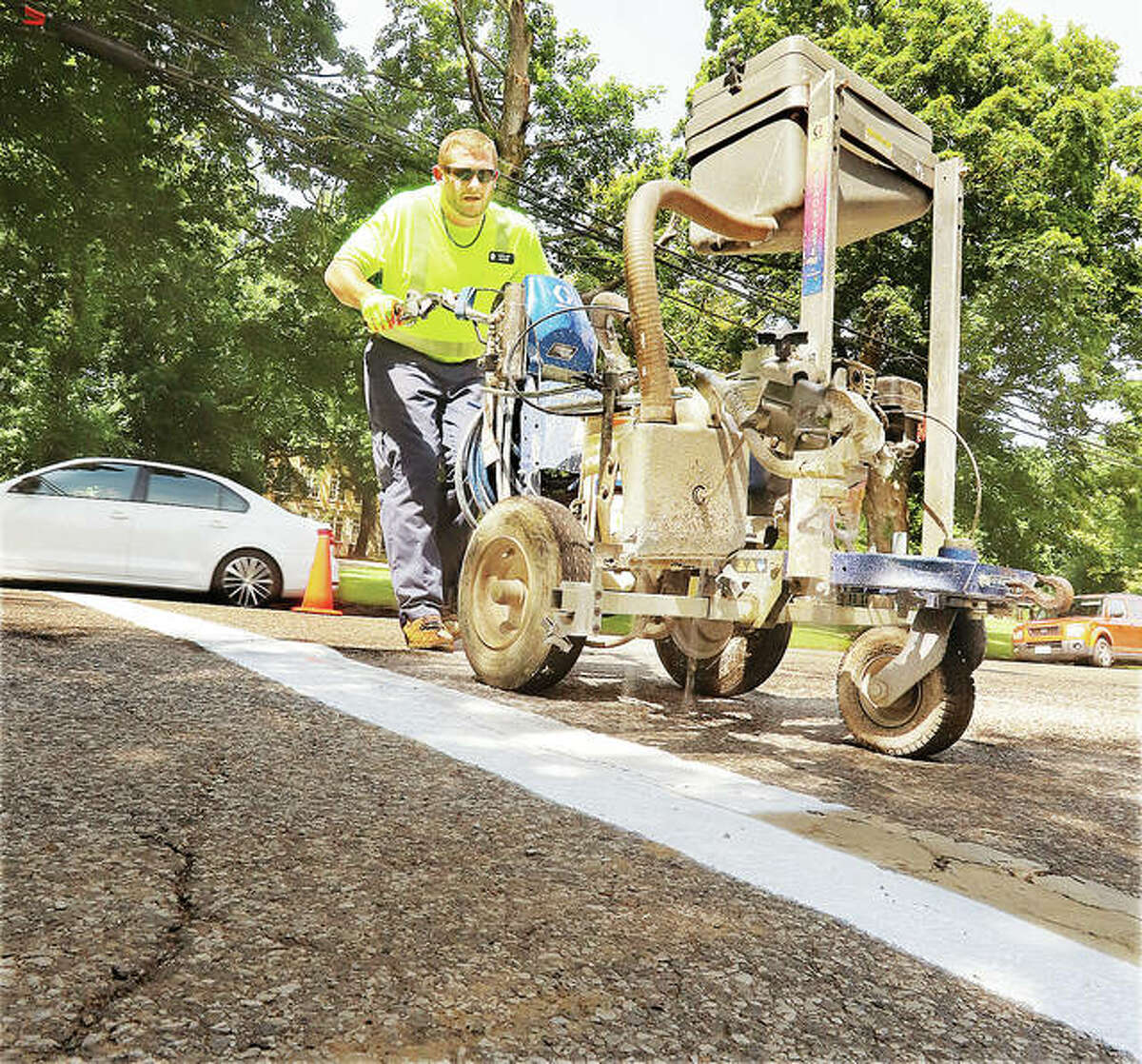 Alton Public Works employee Cory Van Doren paints the white stripes across State Street in Alton this week near West Elementary School. The annual chore, done most years just before school is ready to start, makes the crosswalks more visible.