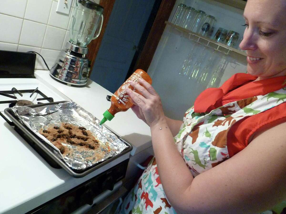 """Biologist Jenna Jadin prepares roasted cicadas at her Washington, D.C. home in 2013. Jadin wrote """"Cicada-Licious: Cooking and Enjoying Periodical Cicadas"""" in 2004."""