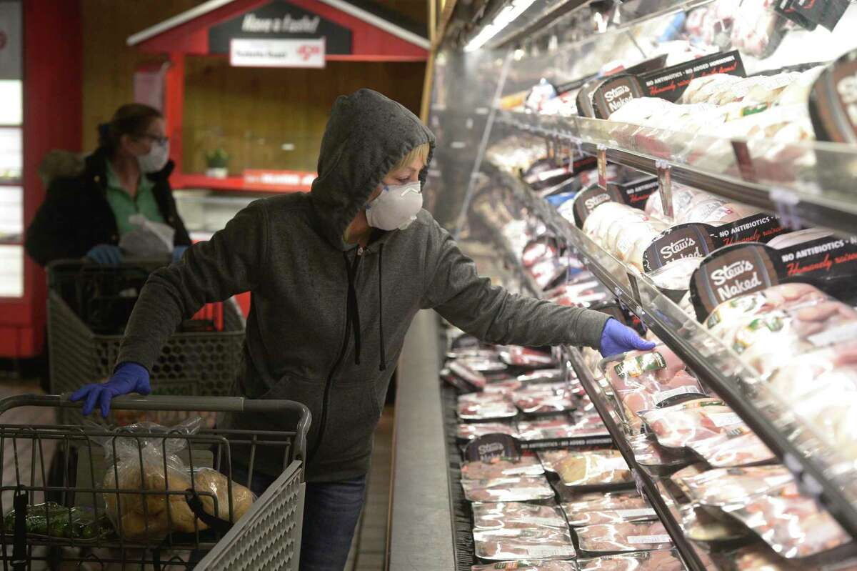 Jane Blackwell, of Brewster, N.Y., wears a mask while shopping at Stew Leonard's in Danbury, Conn., in April 2020.