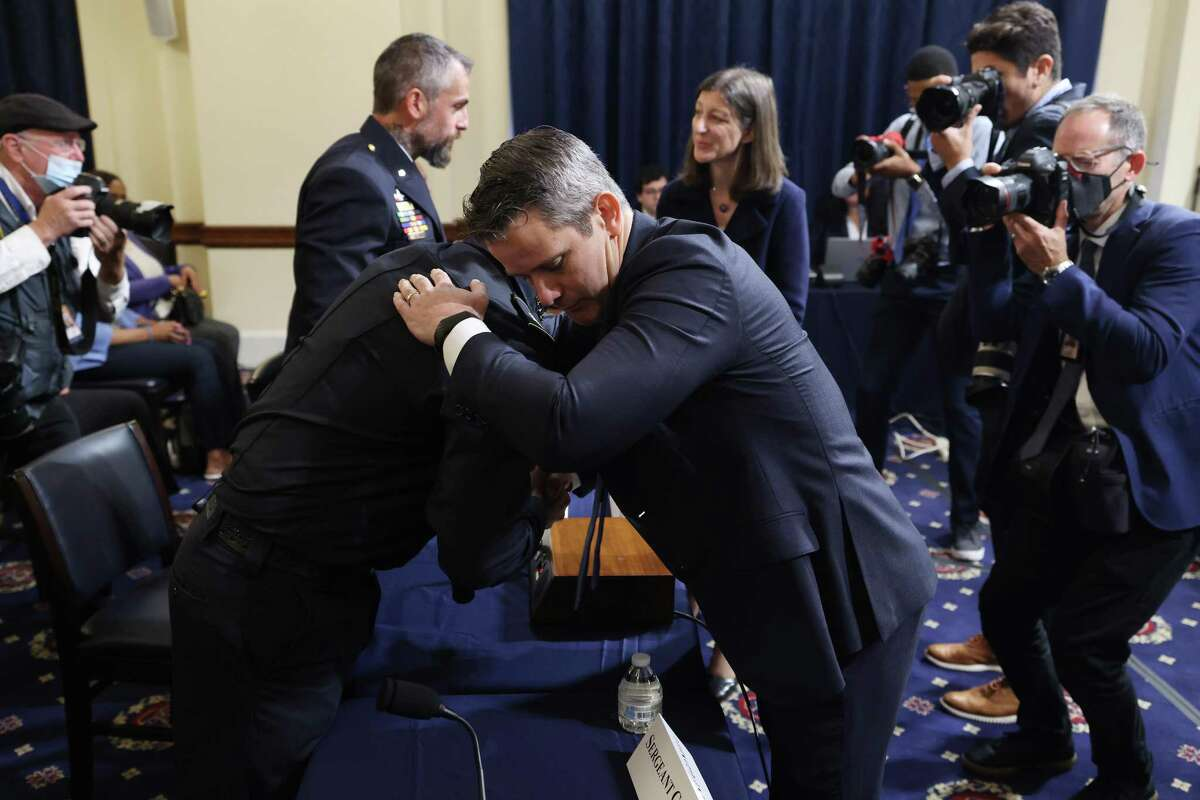 Rep. Adam Kinzinger, R-Ill., right, embraces a Capitol police officer July 27. Kinzinger has stayed true to the tenets of his military service; the same can't be said for his GOP colleagues.