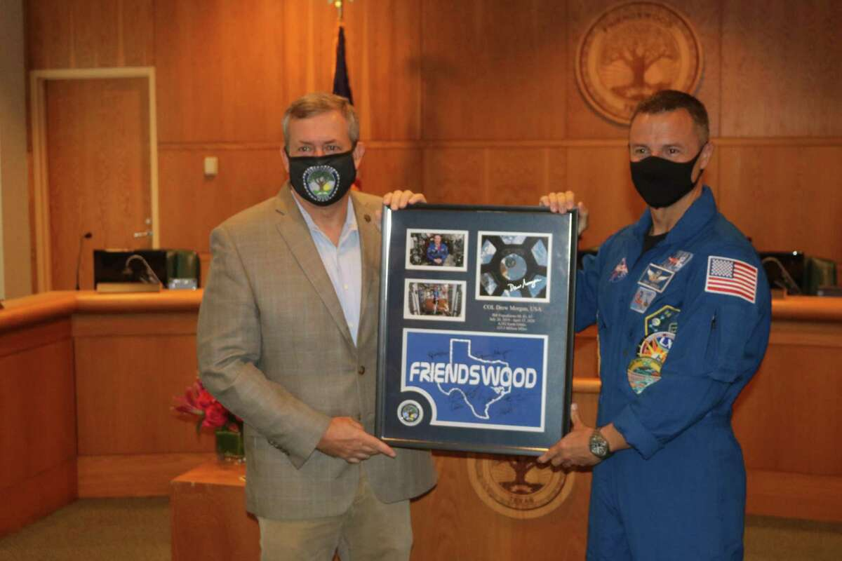 Foreman receives a framed memento from Morgan that includes the Friendswood T-shirt Morgan wore on the International Space Station when he gave a video shout-out to the city.