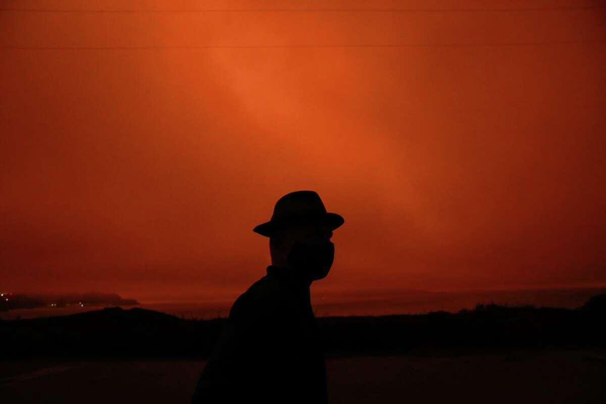 Hanno Botha walks through a park to take photos of smoke-induced dark orange skies that turned day into night in San Francisco on Sept. 9, 2020. The eerie scene was caused by multiple wildfires burning across California and Oregon that month. New research shows a correlation between wildfire smoke and coronavirus infections and deaths.