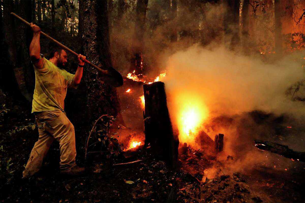 Livermore Ranch worker Jose Vasquez tries to slow the progress of the Glass Fire as it approaches the ranch in Napa County on Oct. 4.