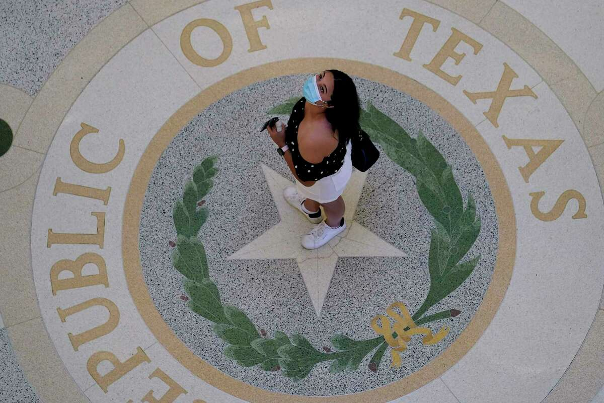 A visitor wears a protective mask during a visit to the Texas Capitol, Thursday, Aug. 12, 2021, in Austin, Texas. Defiance of Texas Gov. Greg Abbott's ban on mask mandates continues as more Texas school districts and communities announce plans to require students to wear face coverings and another county scored a legal victory in its efforts to issue such mandates amid a surge in COVID-19 hospitalizations throughout the state.