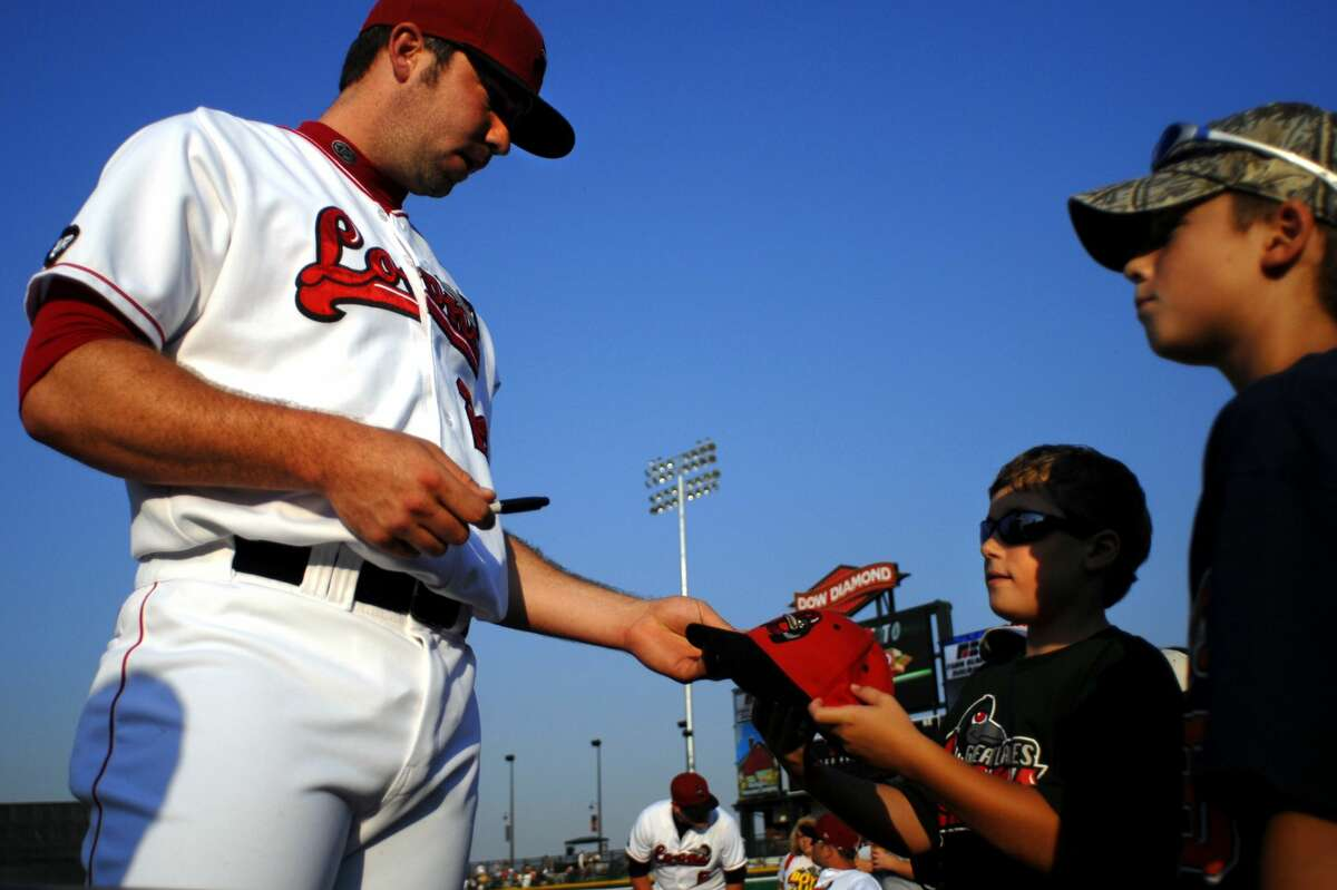 """Great Lakes Loons pitcher Christopher Malone autographs Preston Eurich, 9, of Sebewaing's hat while his brother Connor Eurick, 11, right, watches on before the game at Dow Diamond Tuesday August 28, 2007. """"It is pretty cool that you don't have to have a special pass to get autographs,"""" Connor Eurick said. (Daily News file/Alex Stawinski)"""
