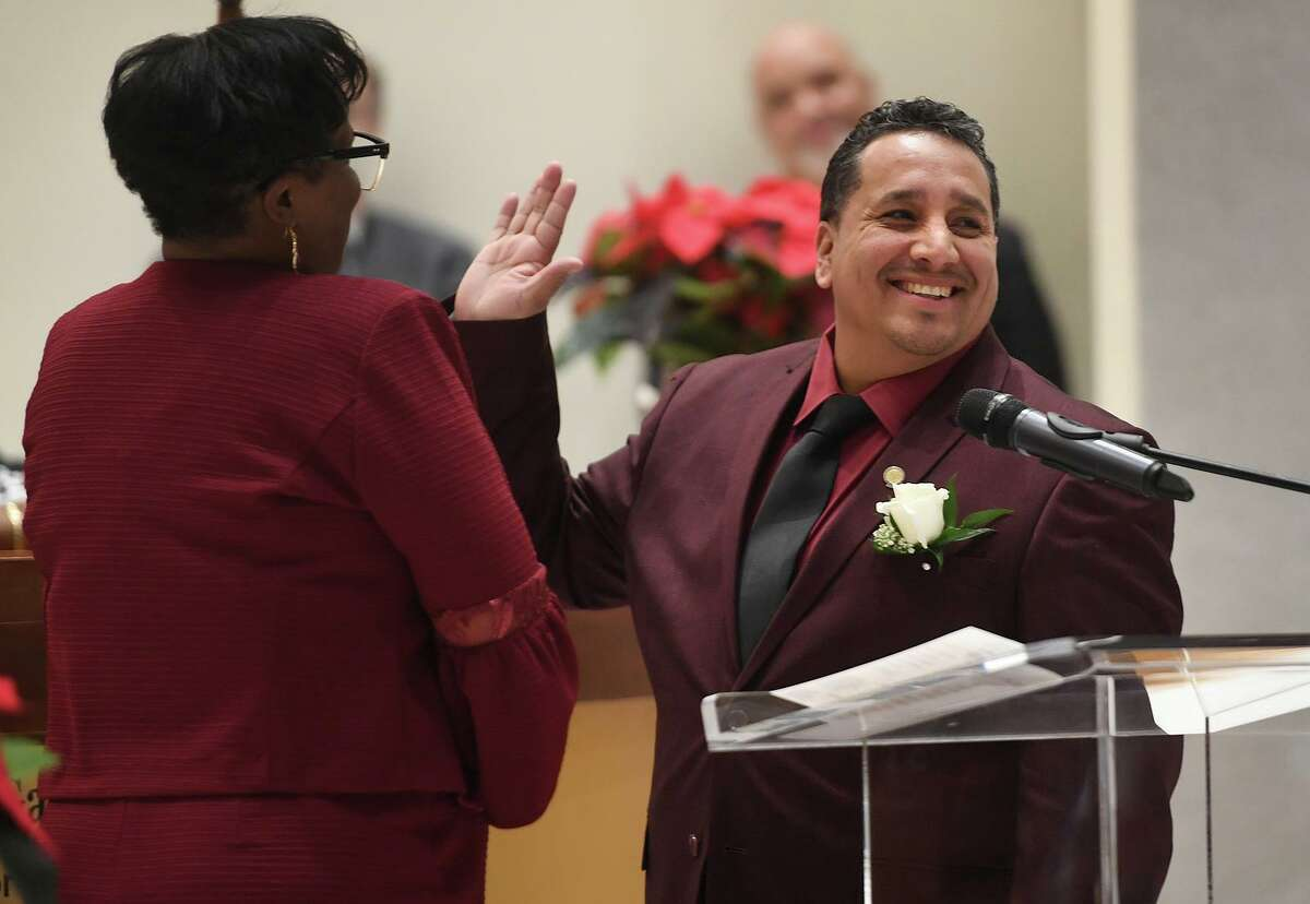 City Councilman Alfredo Castillo smiles toward the crowd as he is sworn in by Wanda Geter during the swearing in ceremony of city officials at City Hall in Bridgeport, Conn. on Thursday, November 28, 2019.