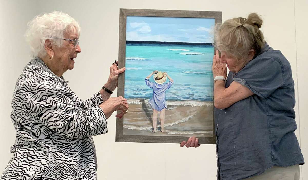 """Juror Betty Iles, left, and Lynne Lokensgard discuss an entry in the Beaumont Art League's """"Landscapes and Seascapes"""" show, on Aug. 8, 2021. The exhibition opens Aug. 14. Photo by Andy Coughlan"""