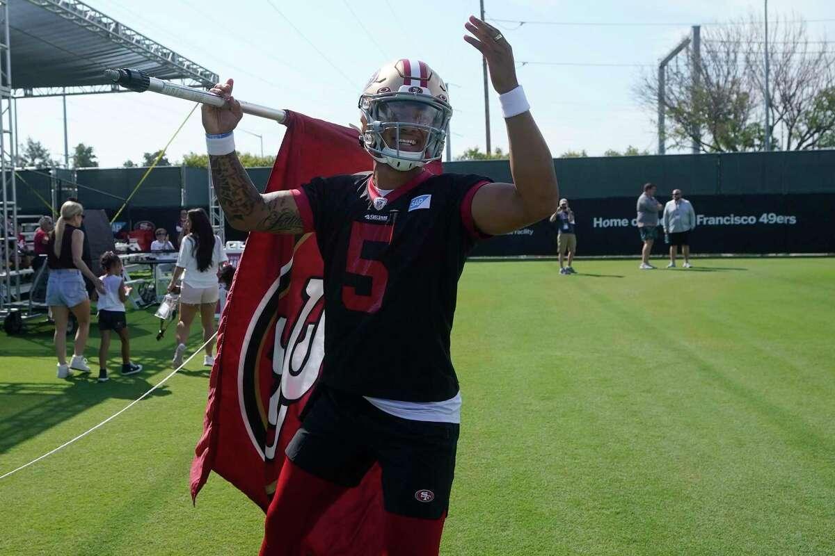 San Francisco 49ers quarterback Trey Lance waves a flag toward fans watching players warm up at NFL football training camp in Santa Clara, Calif., Thursday, July 29, 2021. (AP Photo/Jeff Chiu)