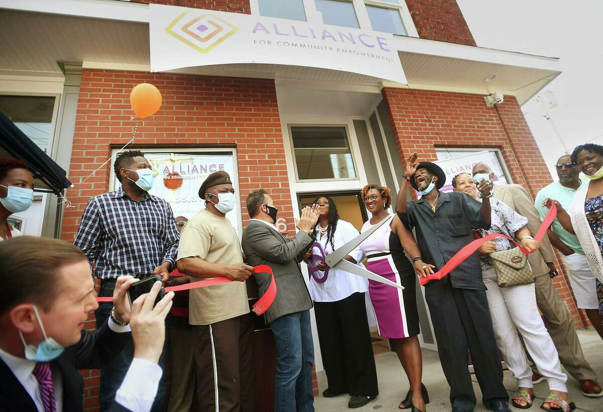 Executive Director Monette Ferguson cuts the ribbon on a new neighborhood office of Alliance for Community Empowerment, formerly ABCD, at 1376 Stratford Avenue in Bridgeport, Conn. on Wednesday, August 11, 2021.