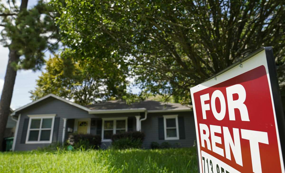 A sign is displayed outside a home for rent.
