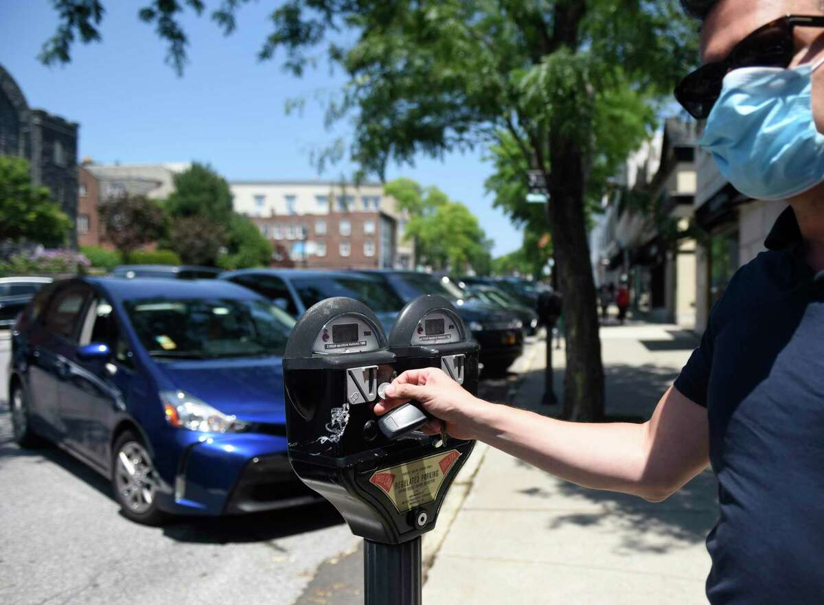 Stamford's Felice Donatiello puts a coin in a parking meter along Greenwich Avenue in downtown Greenwich, Conn. Monday, July 6, 2020. The town is looking to promote its permit program for downtown residents and businesses to keep those short-term spots open for customers like Donatiello.