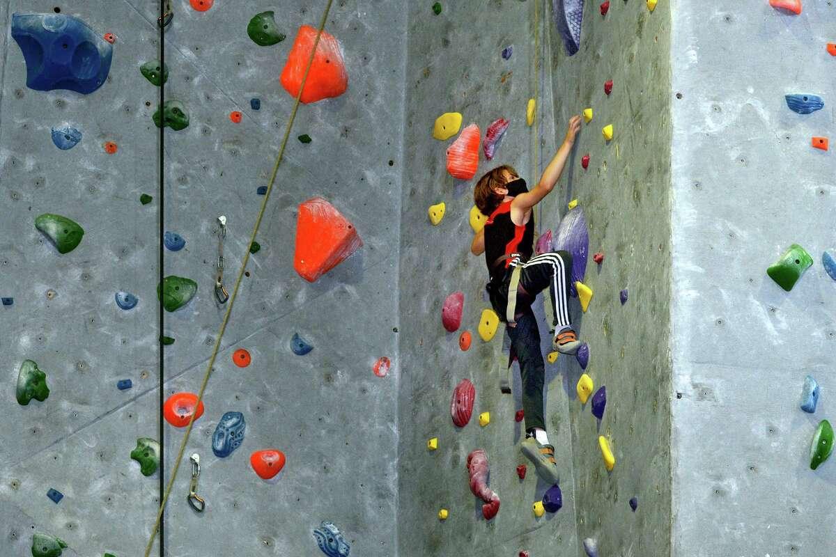 Gabriel Milne, visiting from Vermont, practices his climbing skills at Rock Climb Fairfield, in Fairfield, Conn. Aug. 13, 2021.
