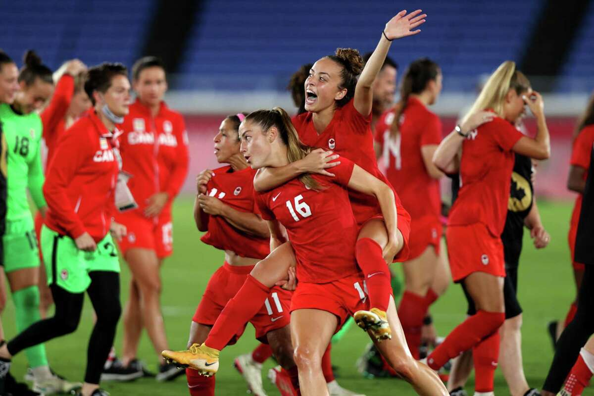 Janine Beckie celebrates with Julia Grosso following their victory to gold medal in the Gold Medal Match Women's Football match between Canada and Sweden at International Stadium Yokohama on August 06, 2021 in Yokohama, Kanagawa, Japan.