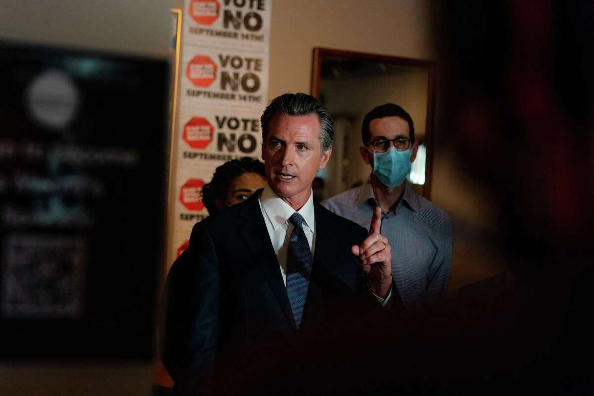 """Gov. Gavin Newsom speaks to reporters during a press conference for his """"Vote No"""" camapaign at Manny's in San Francisco."""