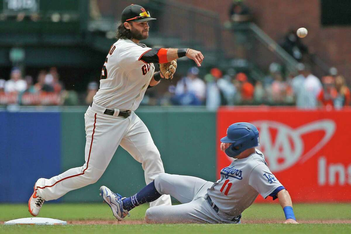San Francisco Giants shortstop Brandon Crawford forces out Los Angeles Dodgers A.J. Pollock (11) and throws to first for the double play in the fifth inning at Oracle Park on July 29, 2021, in San Francisco.