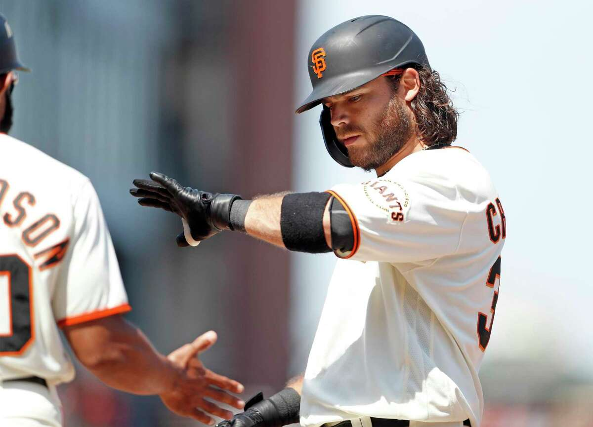 Giants shortstop Brandon Crawford, slapping hands with first base coach Antoan Richardson during a July game, is hitting .297 through Sunday, far above his career best of .275 in 2016.