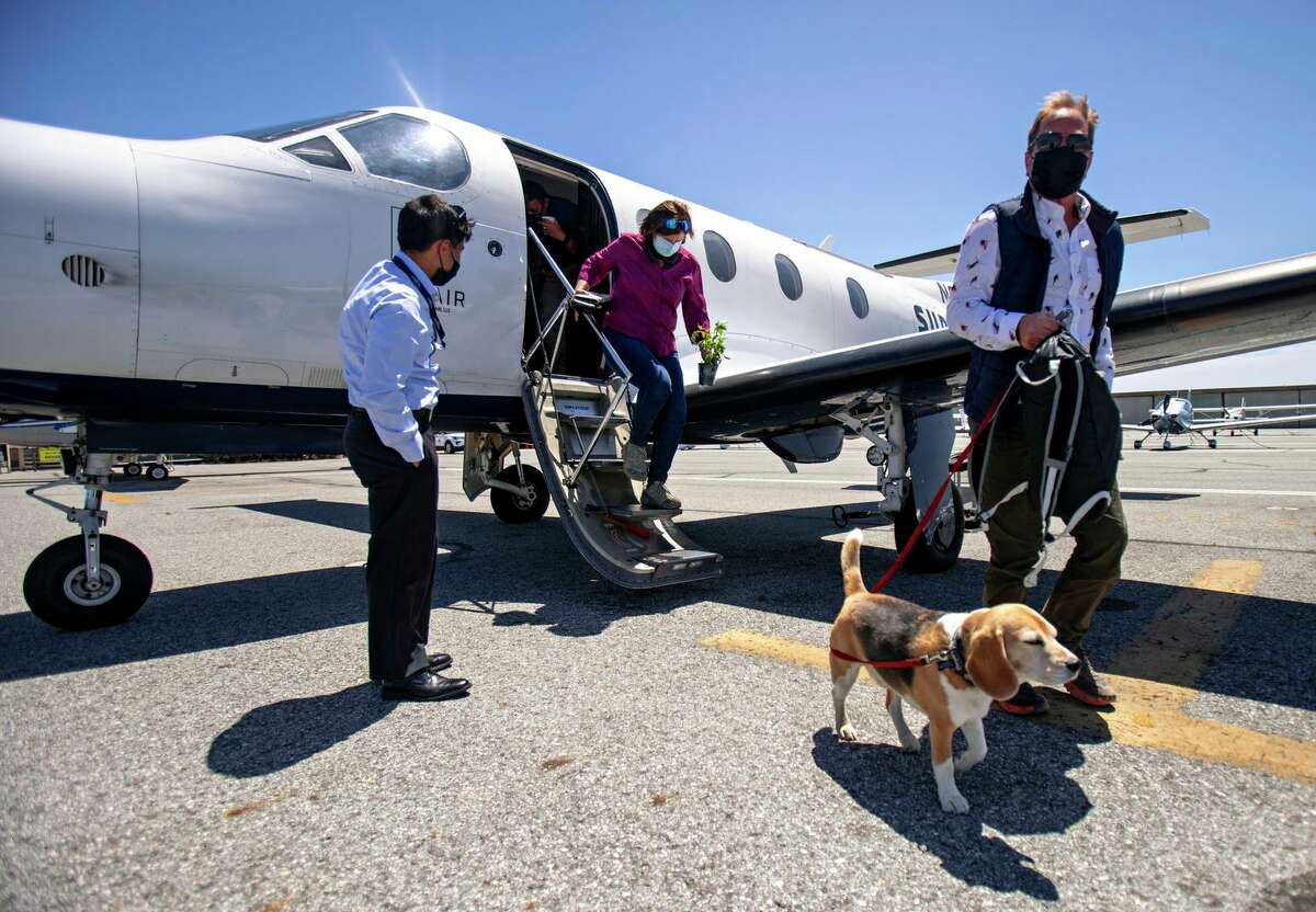 SurfAir passenger Darwin leads Marty and Anne Putnam off the plane after landing in San Carlos.