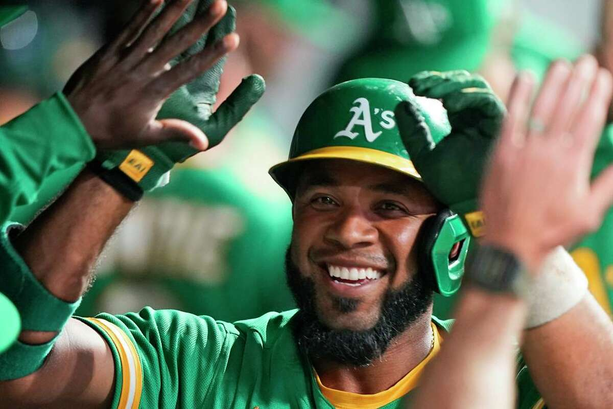 Oakland Athletics' Elvis Andrus is congratulated by teammates after hitting a solo home run during the eighth inning of the team's baseball game against the Cleveland Indians, Wednesday, Aug. 11, 2021, in Cleveland. (AP Photo/Tony Dejak)