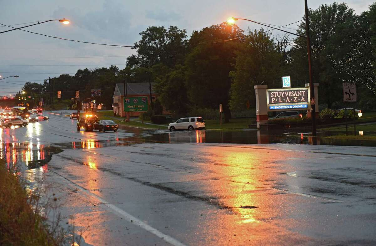 A tow truck pulls away with a car which got stuck in the flooded Western Ave. section in front of Stuyvesant Plaza on Friday, Aug. 13, 2021 in Guilderland, N.Y. Rainfall hit the Capital District from Thursday night to early Friday morning.