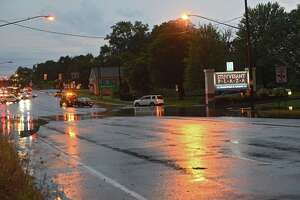 A tow truck pulls away with a car which got stuck in the flooded Western Ave. section in front of Stuyvesant Plaza on Friday, Aug. 13, 2021 in Guilderland, N.Y. A thunderstorm with heavy rains passed through the Capital District.