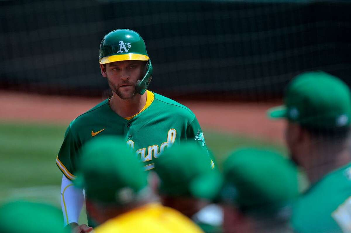 Chad Pinder (4) returns to the dugout after scoring on a wild pitch by Steve Cishek (40) in the sixth inning as the Oakland Athletics played the Los Angeles Angels at the Coliseum in Oakland, Calif., on Wednesday, June 16, 2021. The A's defeated the Angels 8-4.