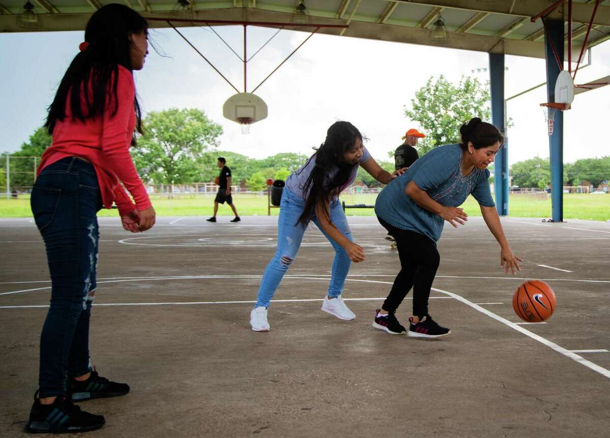 Angelica Yac, right, dribbles the basketball while her daughter Angie Yac, 18, plays defense as they enjoy the afternoon together at Burnett Bayland Park, Friday, Aug. 13, 2021, in Gulfton.