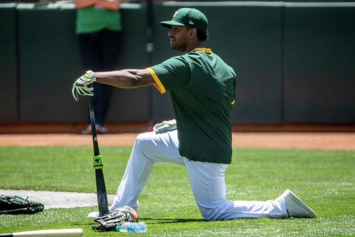 Oakland A's left fielder Khris Davis stretches during an Oakland A's training camp workout at O.Co Coliseum in Oakland, Calif. Tuesday, July 7, 2020. Due to COVID-19, the 2020 MLB season has been postponed with players just beginning to return for warmups and practices while wearing masks and keeping social distance.