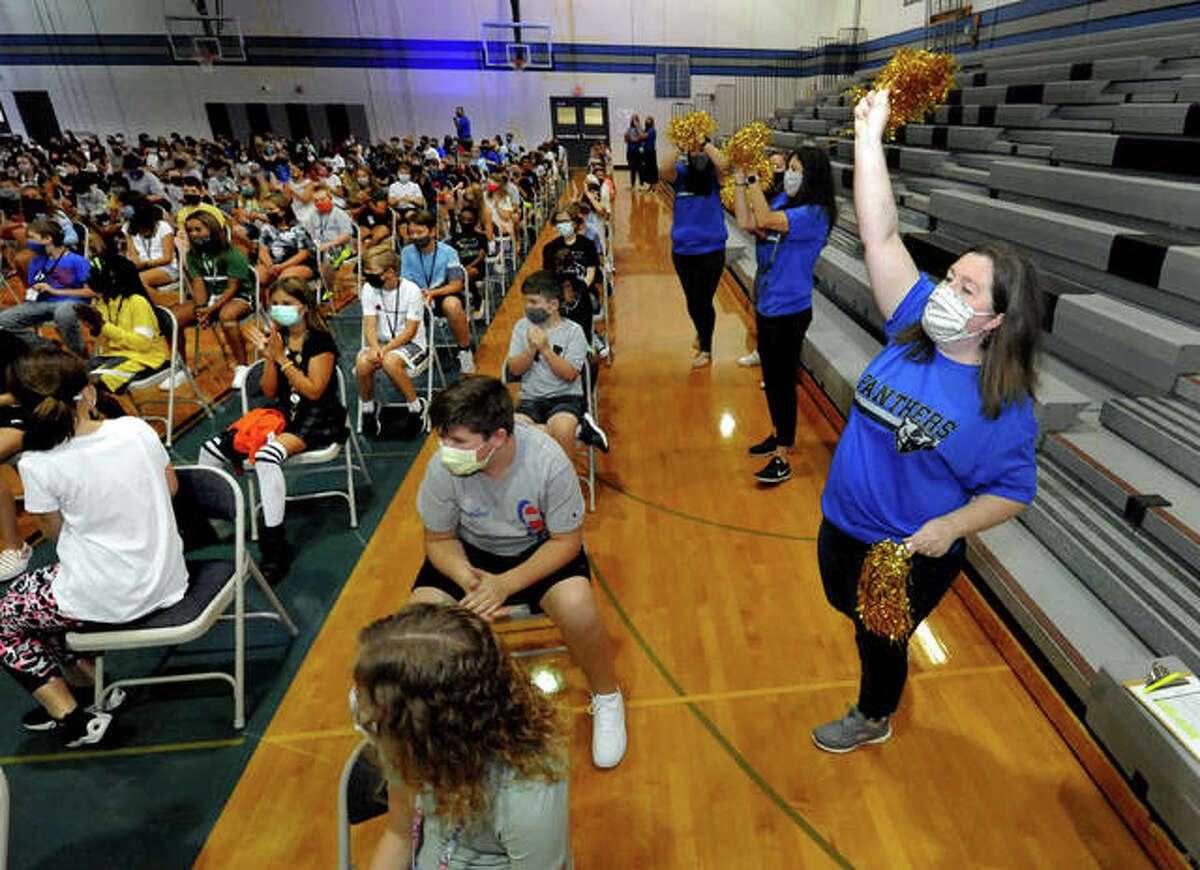 Sixth-grade Liberty Middle School teacher Sarah Hollis, right, whips up the crowd of students with a cheer during a welcome assembly Wednesday.