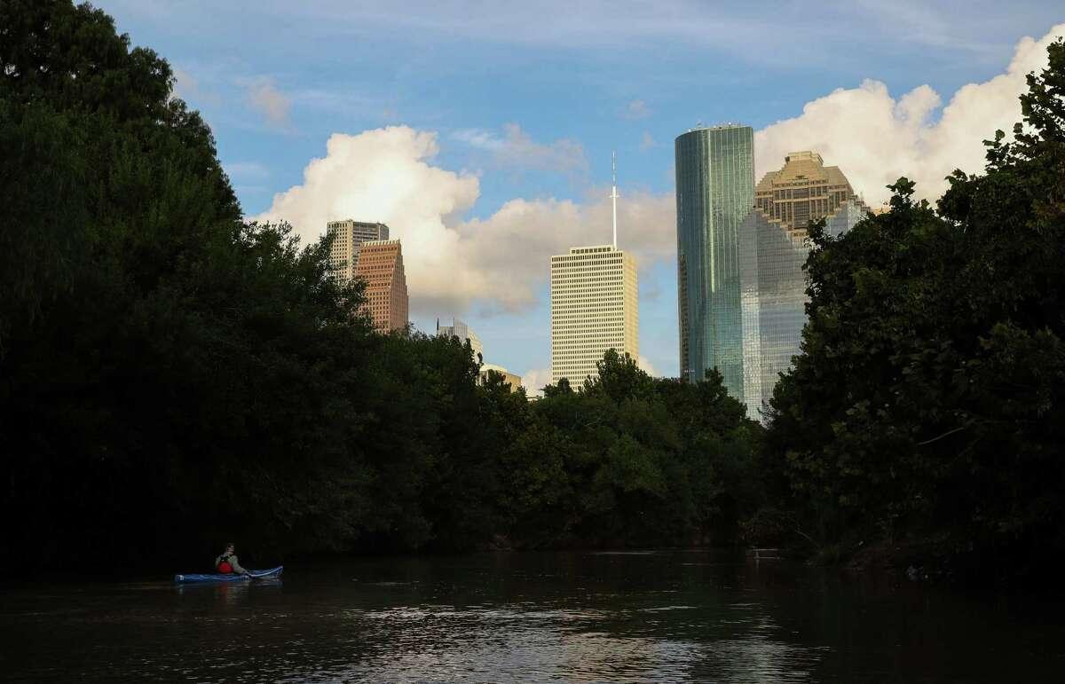 Bruce Bodson kayaks near downtown Sunday, Aug. 8, 2021, in Buffalo Bayou in Houston.