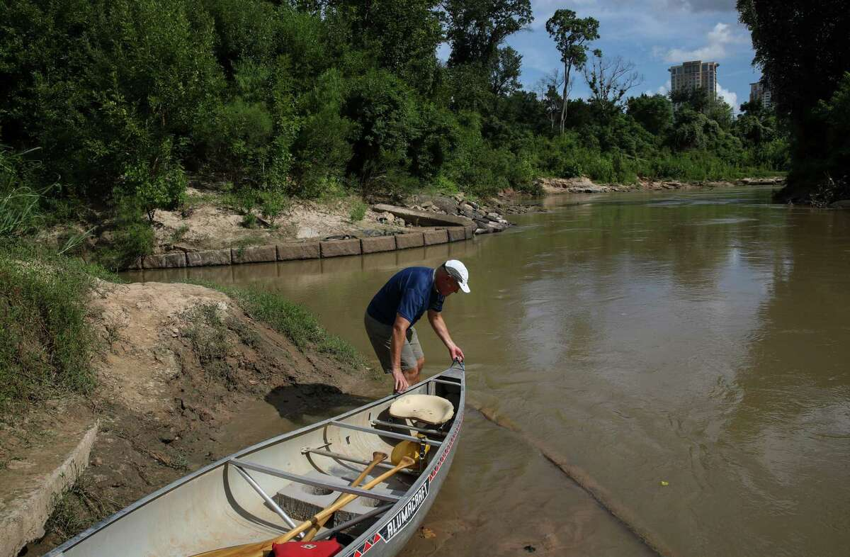 Tom Helm loads a canoe into Buffalo Bayou on Sunday, Aug. 8, 2021, in Houston.