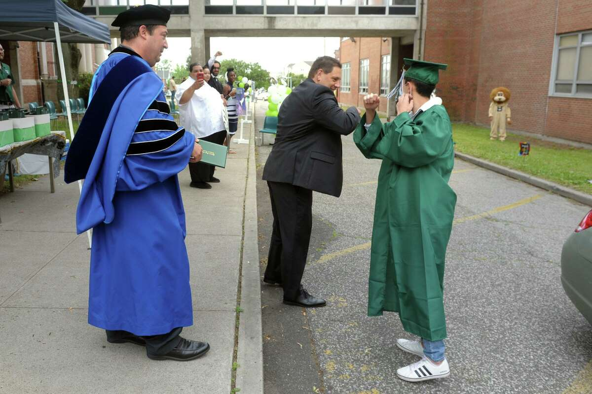 Then-Acting Superintendent of Schools Michael Testani exchanges an elbow bump with Ali Alokla as he steps forward to receive is diploma during graduation for the Bassick High School Class of 2020, in Bridgeport, Conn. June 18, 2020. Testani, now the superintendent, is not alarmed about low vaccination rates in Bridgeport because he found low levels of transmission when students were together over the last year even without the vaccination.
