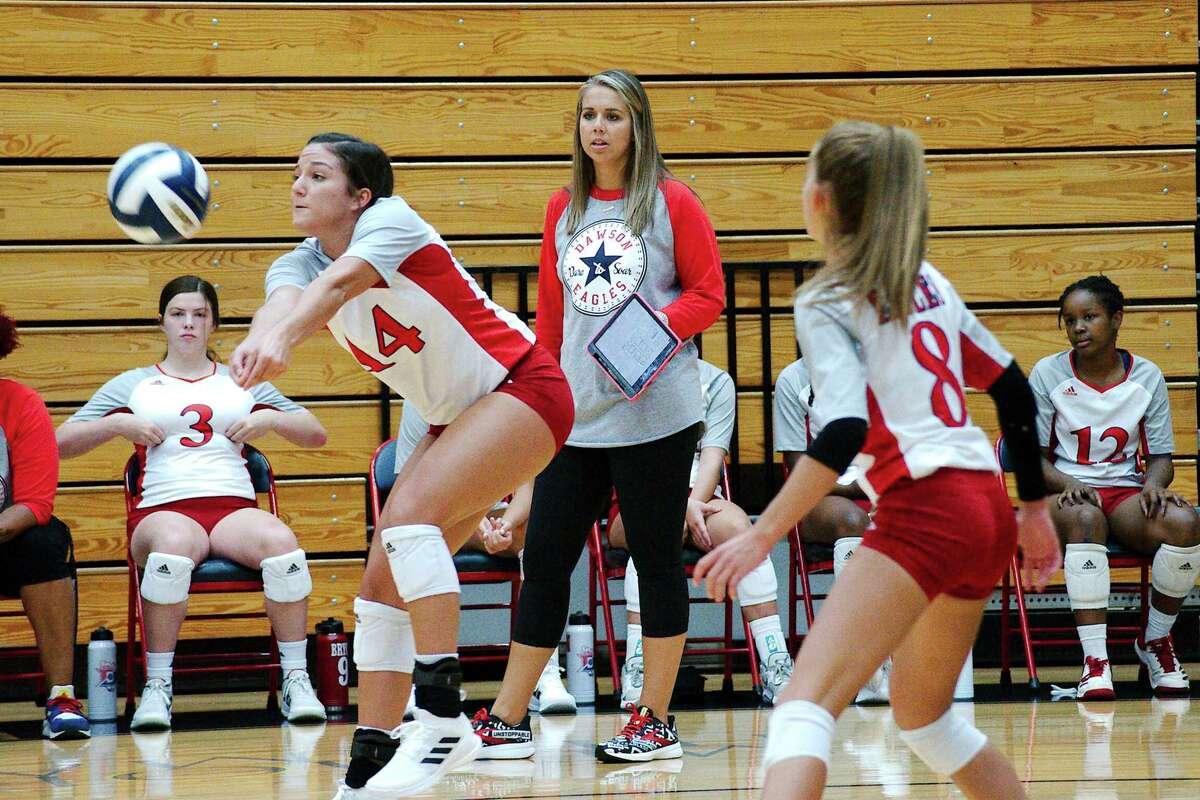 Dawson volleyball coach Lauren Leth watches as Dawson's Kylie Nance (14) sets the ball against Atascocita Friday at Dawson High School.