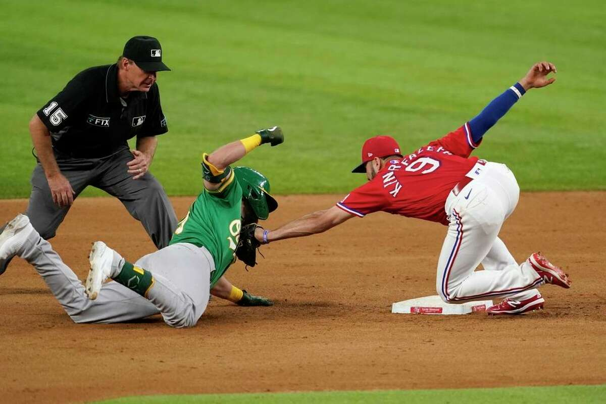 Oakland Athletics' Seth Brown, center, is tagged out by Texas Rangers third baseman Isiah Kiner-Falefa (9) as umpire Ed Hickox (15) watches in the eighth inning of a baseball game in Arlington, Texas, Friday, Aug. 13, 2021. Brown was tagged out while attempting to stretch out a run-scoring double that scored Matt Chapman. (AP Photo/Tony Gutierrez)