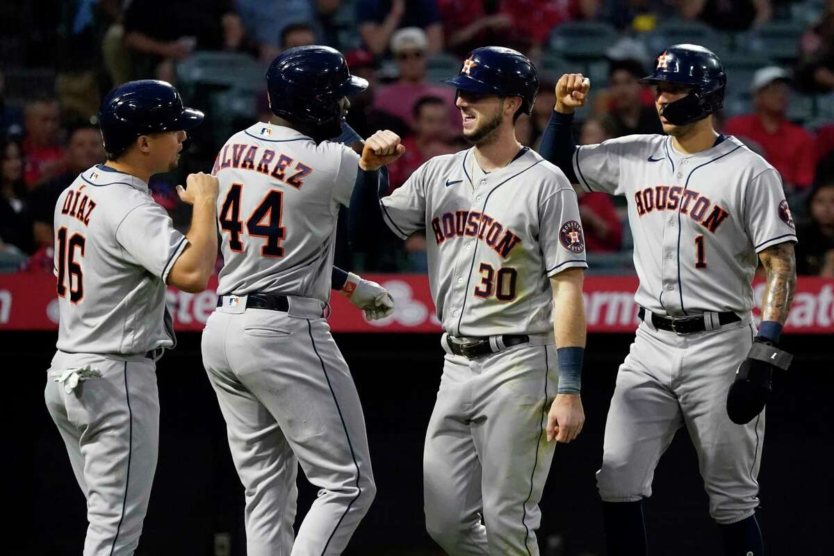 Houston Astros' Kyle Tucker (30) celebrates after driving in Aledmys Diaz (16), Yordan Alvarez (44) and Carlos Correa with a grand slam during the fourth inning of the team's baseball game against the Los Angeles Angels on Friday, Aug. 13, 2021, in Anaheim, Calif. (AP Photo/Marcio Jose Sanchez)