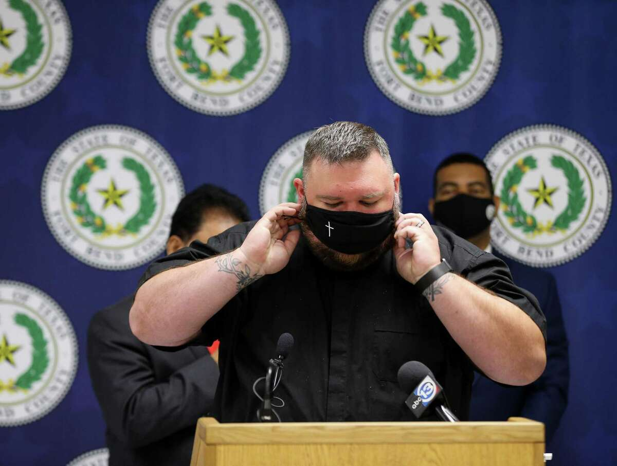 St. Martin's Lutheran Church senior pastor Will Starkweather puts his face mask back on after he led a prayer at a news conference in which county judge KP George announced the COVID-19 risk level has been increased for the county on Tuesday, Aug. 3, in Richmond.