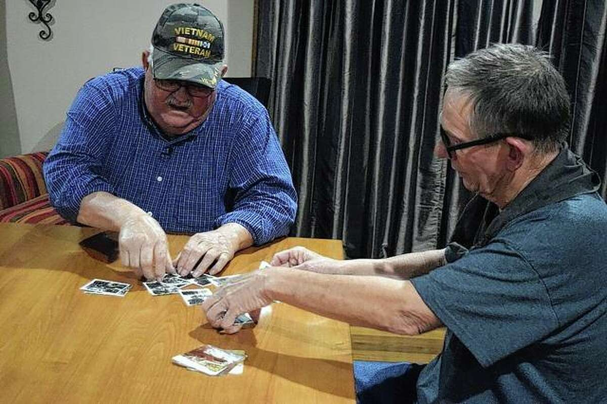 Dale Edge (left) and Fred Kjorlien talk about the people they knew while looking at pictures from their service in Vietnam.
