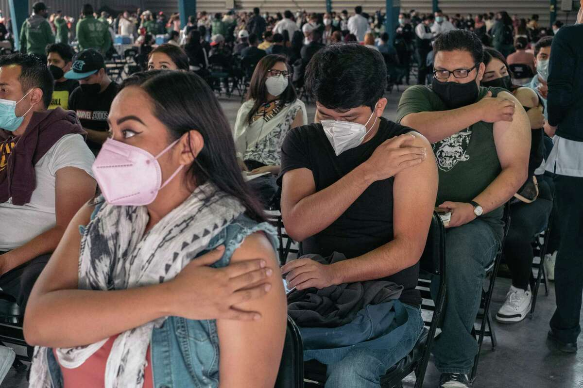 People wait in an observation area June 28 after receiving a dose of the Sinovac Biotech vaccine at a site open to ages 18 to 29 in Mexico City.