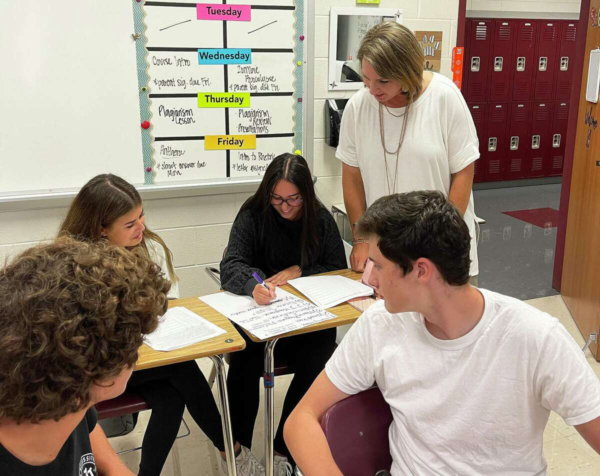 Magnolia High School teacher Kristen Saldana looks over the shoulder of one of her students as they work on the first day of class for the new year. Saldana said students were eager to return to normal.