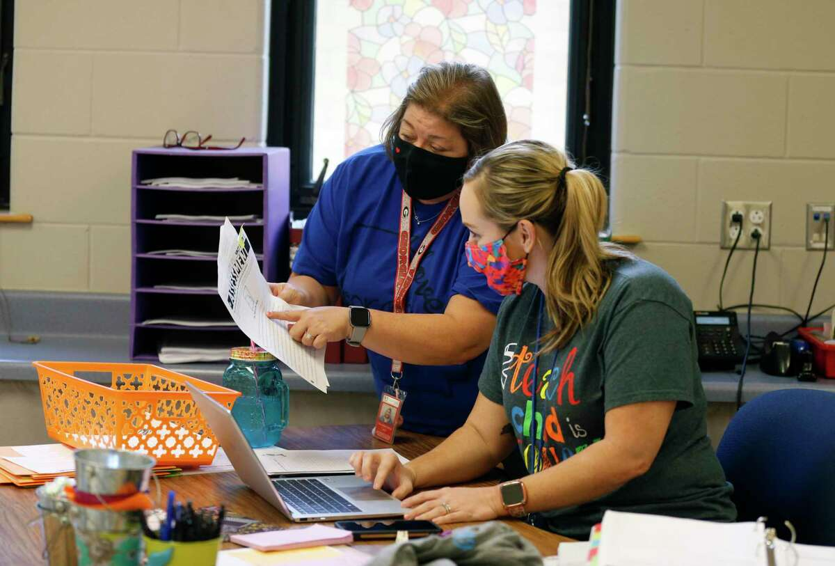 Allison Martino and Joy Crawford go over plans Friday for the first day of school at Lackland ISD, set for Monday. Students at the three school districts on Joint Base San Antonio will stay masked regardless of the outcome of a court battle between local and state officials.