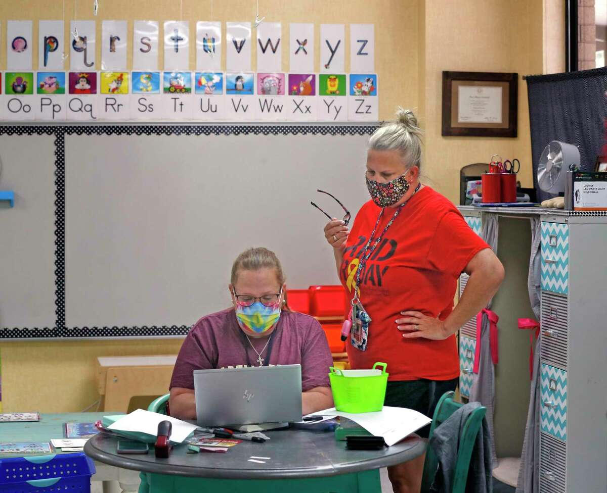 Pre-K teacher Allison Archibald Ormon, left, and Kasandra Smith go over plans Friday for the first day of school at Lackland ISD, set for Monday. Students at the three school districts on Joint Base San Antonio will stay masked regardless of the outcome of a court battle between local and state officials.