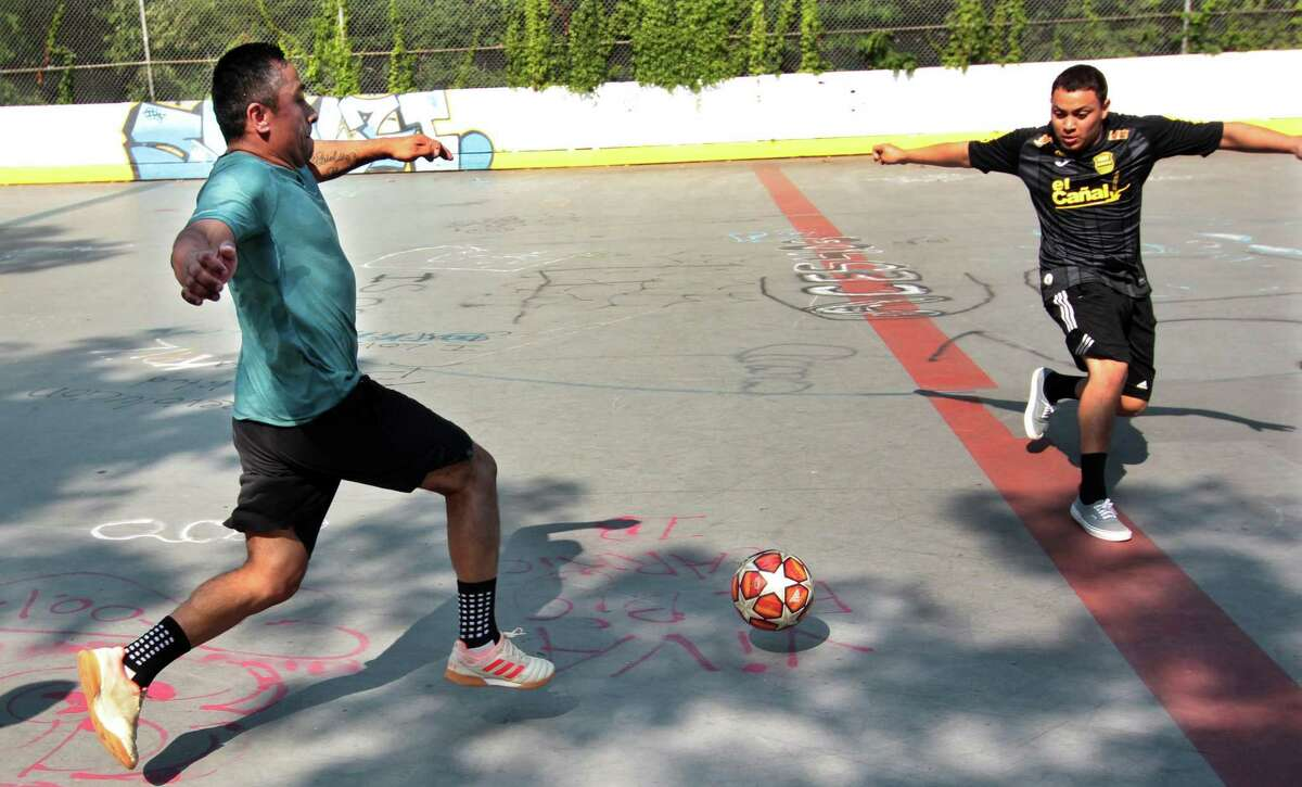 Cesar Chinchai, left, and Danny Tesla, members of the team Latinos United, converge on the ball as they play a soccer match with friends at the ice rink at Scalzi Park in Stamford, Conn., on Saturday August 6, 2021. His mom Sophia made sure he had all the right protection since he is new to the sport.