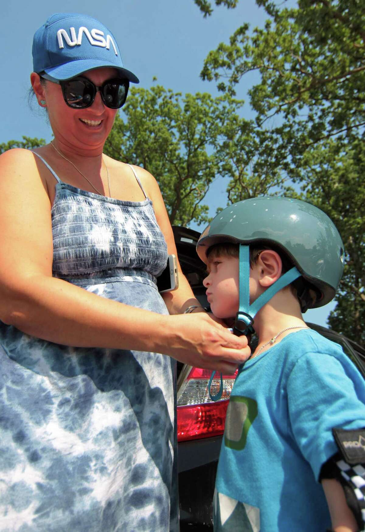 Nico Bakuradze, 4, gets help with his helmet from his mom Sophia before he plays at the skateboarding park at Scalzi Park in Stamford, Conn., on Saturday August 6, 2021.