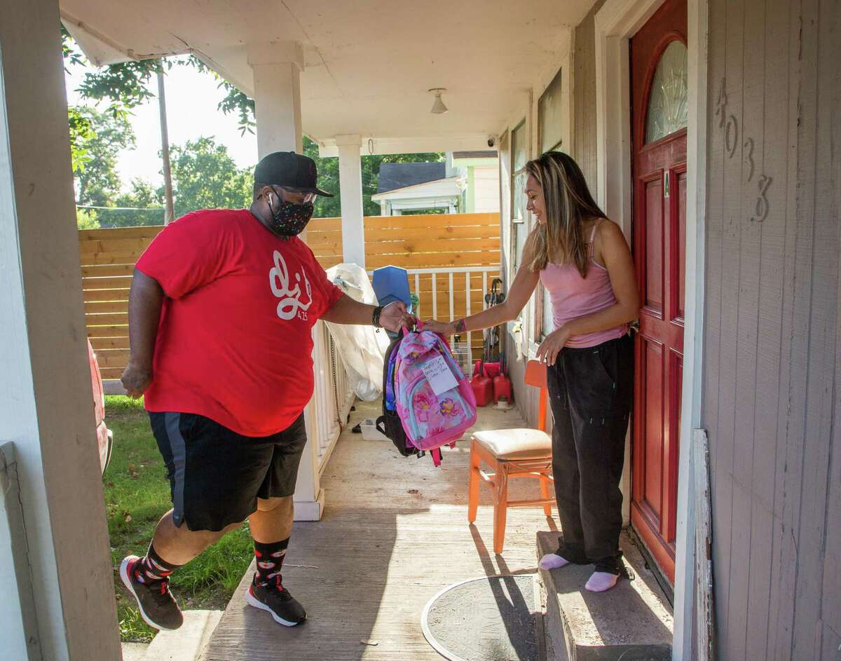 Jermaine Williams, who performs at private events as DJ 425, delivers backpacks to Teresa Gonzales, a mother of three, in Houston on Saturday.