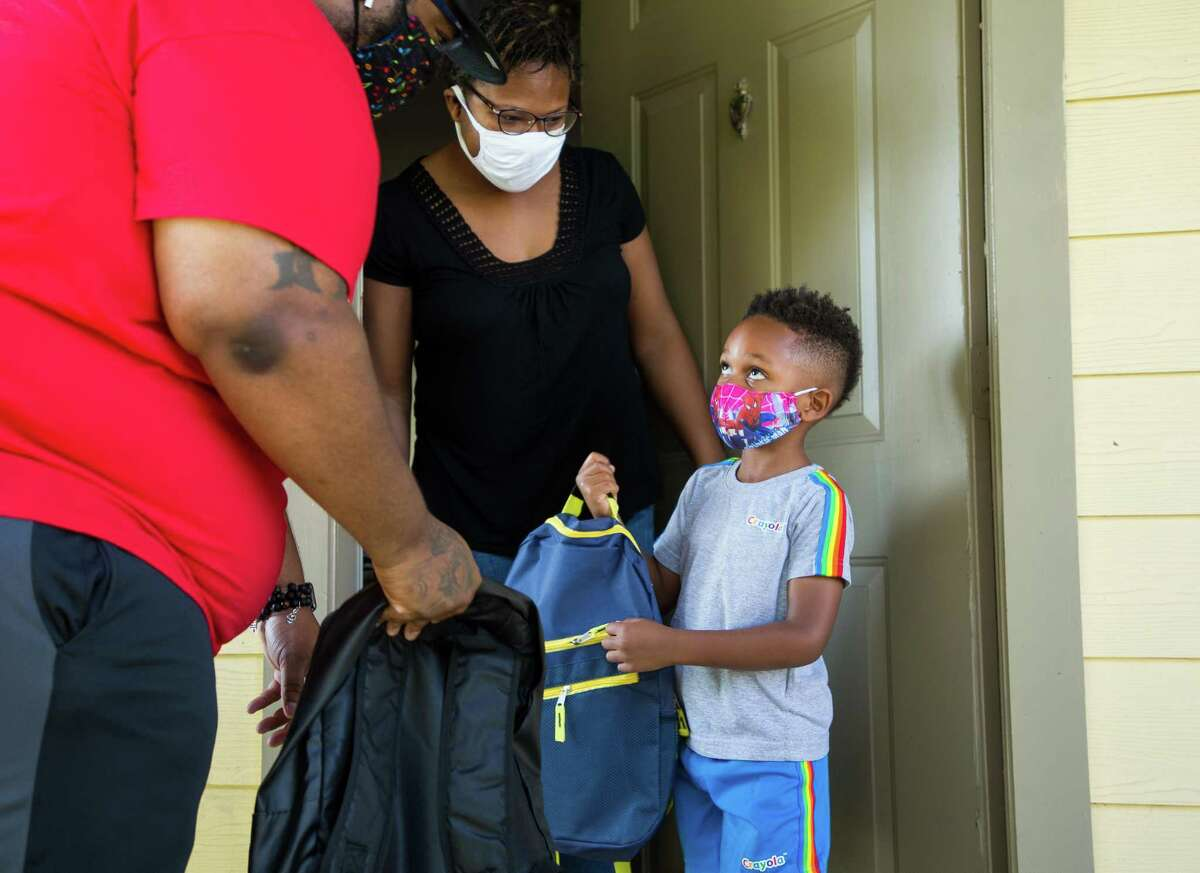 Jermaine Williams, left, delivered backpacks to Monica Jackson and her son Keelan, 4, on Saturday, Aug. 14, 2021, in Houston. Williams and his wife Chandress raised money to buy backpacks and school supplies for 40 students.