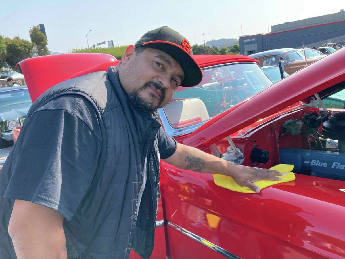 Francisco Pintor of South San Francisco wipes down his 1954 Chevrolet Impala on Saturday, Aug. 14, 2021, at a low-rider car show in Daly City, Calif.