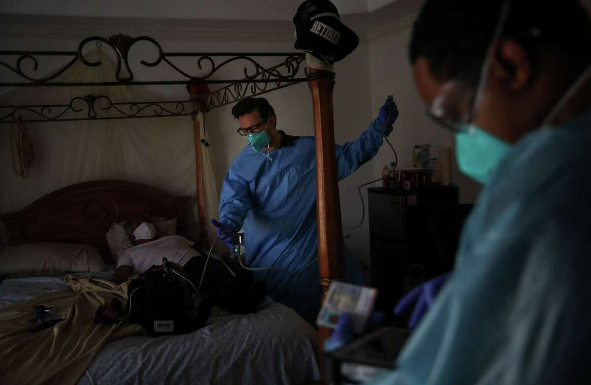 Houston Fire Department Captain Daniel Soto, center, and another firefighter prepare to transport a man who is experiencing symptoms of COVID-19 to a hospital Thursday, Aug. 5, 2021, at a home in Houston.